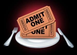 "Two ""Admit One"" dinner show tickets on a dinner plate"
