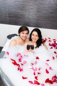 Romantic couple sipping wine in their Pigeon Forge hotel room with a Jacuzzi