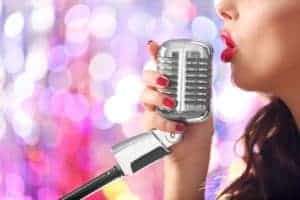 Woman singing into a retro microphone.